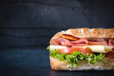 submarino: Pan Ciabatta relleno con queso, carne y verduras en el fondo oscuro, el enfoque selectivo y espacio en blanco