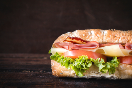 dinner menu: Ciabatta sandwich on wooden background with blank space gor the text