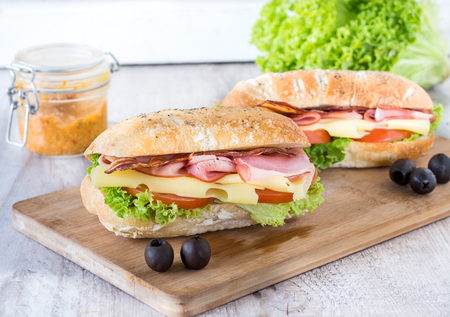 Ciabatta sandwich with bacon and cheese on wooden boarde,selective focus photo
