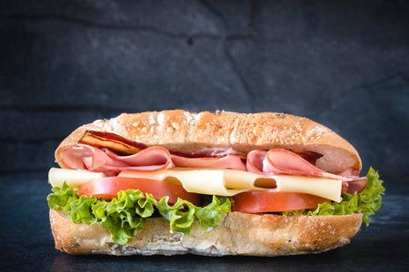 Big ciabatta sandwich with meat and cheese on dark background photo