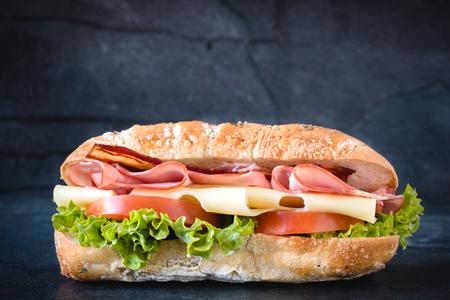 Grote ciabatta broodje met vlees en kaas op donkere achtergrond