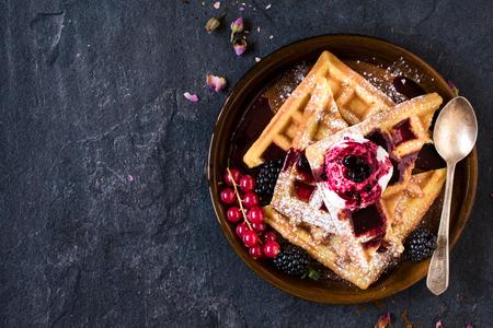 breakfast: Gofres belgas tradicionales con helado y salsa de frutas de bayas en el plato, enfoque selectivo y espacio en blanco