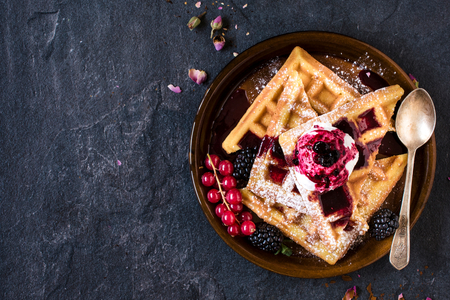above: Traditional Belgian waffles with ice cream and berry fruit sauce in the plate,selective focus and blank space Stock Photo