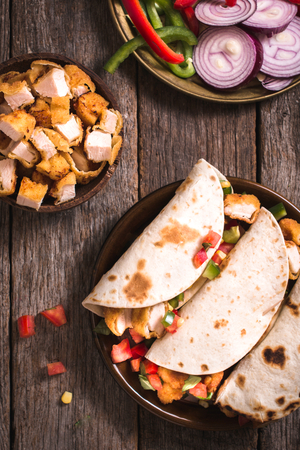 tortilla wrap: Tortilla wrap sandwiches with fried chicken and vegetables on wooden background,selective focus