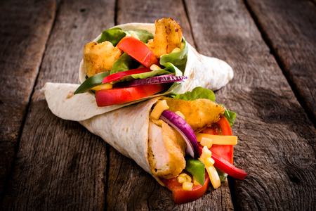 chickens: Tortilla wrap sandwich with fried chicken and vegetables on wooden background,selective focus Stock Photo