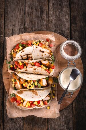 tortilla wrap: Tortilla wrap sandwiches with fried chicken and vegetables from above on wooden background,selective focus and blank space