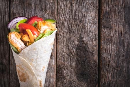 chicken sandwich: Sándwich de envoltura de pollo en el fondo de madera con espacio en blanco