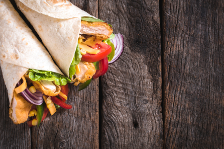 chicken salad: Tortilla sandwiches with fried chicken and vegetables on wooden background with blank space Stock Photo