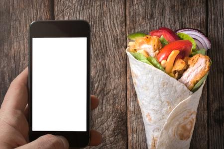 take away: Blank screen on cellphone and tortilla wrap,take away concept Stock Photo
