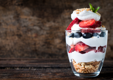 desserts: Sweet dessert in glass with biscuit,berry fruit and whipped cream,selective focus and blank space