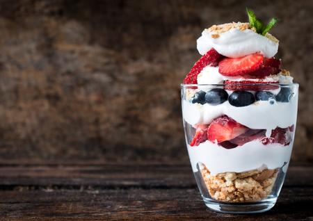 Zoet dessert in glas met biscuit, bessen fruit en slagroom, selectieve aandacht en lege ruimte Stockfoto