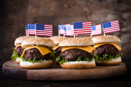 american cuisine: Mini beef burgers with American flag on wooden backgound,selective focus