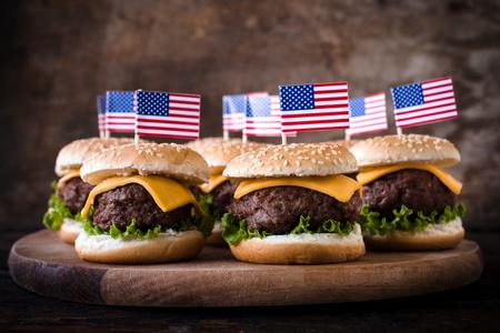 julio: Mini hamburguesas de carne con la bandera americana en el backgound de madera, enfoque selectivo