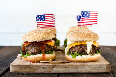 american cuisine: American mini beef burgers with cheese and USA flags on wooden board,selective focus