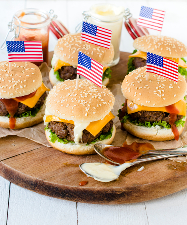 vertica: American mini beef burgers with cheese and USA flags,selective focus