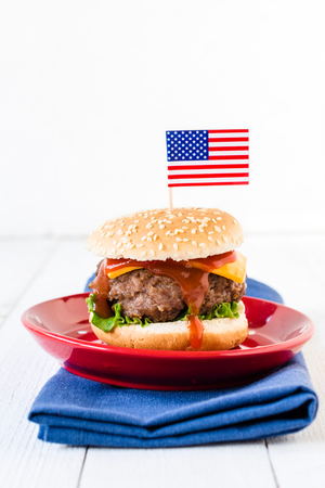 vertica: American mini beef burgers with cheese and USA flags,selective focus and blank space