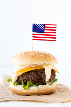 vertica: Single American mini beef burgers with cheese and USA flags,selective focus