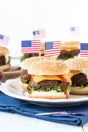 vertica: Mini beef burgers with American flag in plate,selective focus and blank space