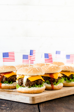 vertica: Mini beef burgers with American flag on wooden board,selective focus and blank space