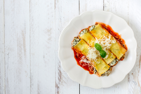 lasagna: Cannoli stuffed with cheese and spinach in tomato sauce,from above and blank space