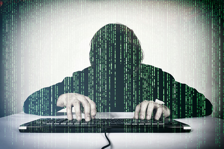 internet attack: Hacker typing on the keyboard and mocking