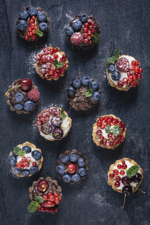 summer pudding: Vanilla and chocolate pudding in mini tarts with berry fruits from above