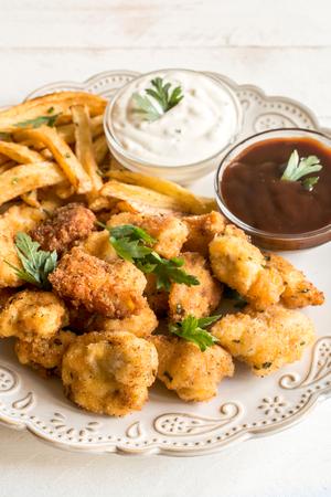 Chicken Nuggets: Placa con nuggets de pollo frito y patatas fritas, enfoque selectivo Foto de archivo