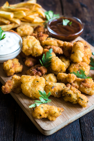 nuggets de poulet: Served chicken nuggets and french sauce on wooden background