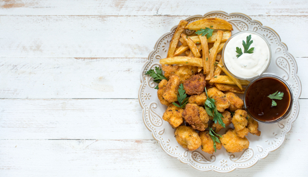 chicken nuggets: Served plate with fried chicken nuggets and french fries,blank space on the left side