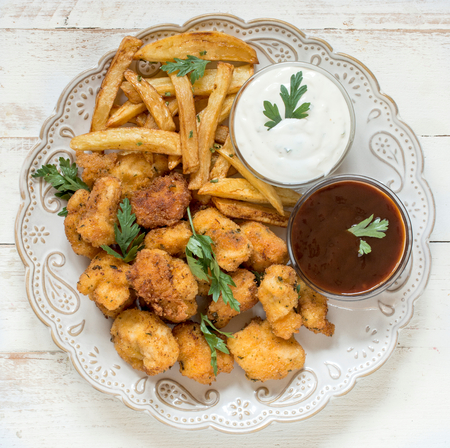 chicken nuggets: Served plate with fried chicken nuggets and french fries Stock Photo