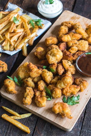 chicken nuggets: Served chicken nuggets and french sauce on wooden board,selective focus Stock Photo