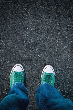 Brand new green shoes from above on asphalt with blank space for text