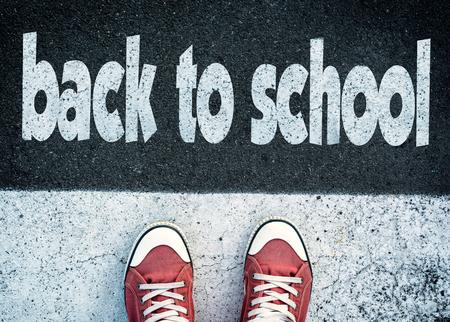 Student die zich boven het teken terug naar school Stockfoto