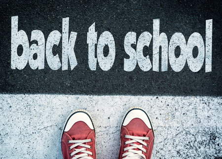 Student standing above the sign back to school Stock Photo