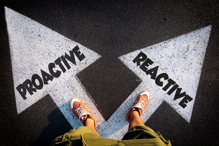 Proactive or Reactive dilemma concept with man legs from above standing on signs Stock Photo