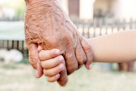 grandparent: Grandchild holding grandparent for the hand,selective focus Stock Photo