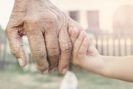 abuelos: Pequeño niño sosteniendo su abuelo por mano, atención selectiva