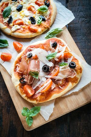 mini pizza: Served prosciutto mini pizza with parmesan cheese on wooden board,selective focus