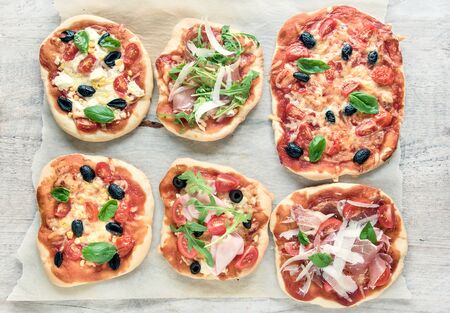 arugola: variety of mini pizzas from above on wooden table Stock Photo