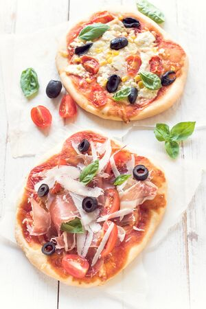 arugola: Served prosciutto mini pizza with parmesan cheese on white wooden background,selective focus