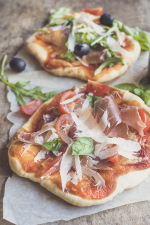 mini pizza: Prosciutto mini pizza with parmesan cheese on wooden background Stock Photo