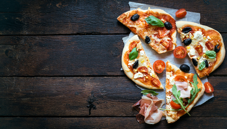 mini pizza: Slices of mini pizza variety served on wooden board and background,from above and blank space Stock Photo