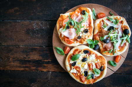 variety of mini pizzas from above on wooden table with blank space