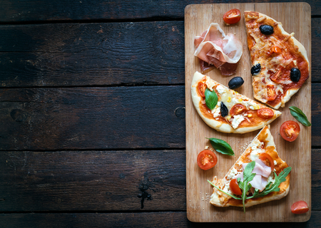 comida italiana: Rebanadas de Mini variedad de pizza que se presentan en la tabla de madera y el fondo, de lo alto y el espacio en blanco Foto de archivo