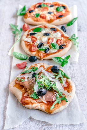 arugola: Mini pizzas served on the table,selective focus Stock Photo