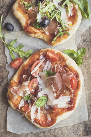 mini pizza: Prosciutto mini pizza with parmesan cheese on wooden background from above Stock Photo