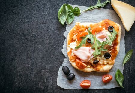 mini pizza: Ham mini pizza on dark background with blank space for your ads Stock Photo