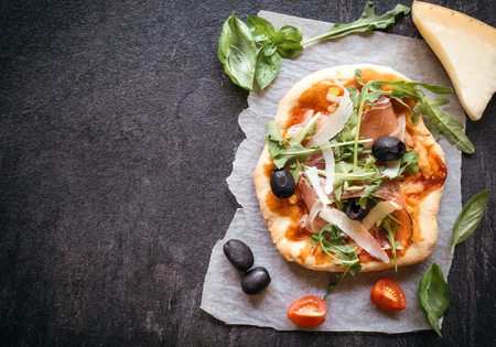 mini pizza: Prosciutto mini pizza with parmesan cheese on dark background with blank space for your ads