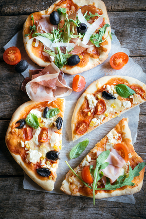 mini pizza: Served prosciutto mini pizza with parmesan cheese on wooden background,selective focus Stock Photo