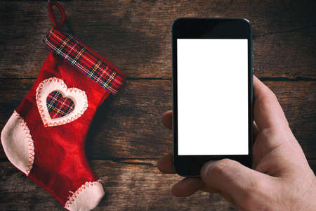 christmas sock: Traditional Christmas sock and blank screen on mobile phone on wooden background